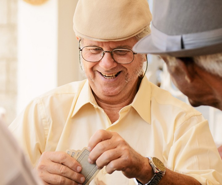 Happy active retired people, old hispanic friends having fun, seniors playing cards at home.